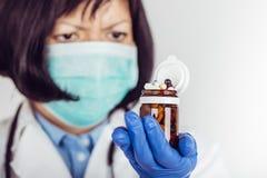Doctor de sexo femenino en la capa blanca del laboratorio y la m?scara m?dica que sostienen la botella de cristal con muchas dive fotografía de archivo libre de regalías