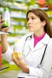 Doctor de sexo femenino en la farmacia que mira la medicina Foto de archivo libre de regalías