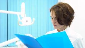 Doctor de sexo femenino en las notas pacientes delante del equipamiento médico, concepto de la lectura del gabinete del dentista  metrajes