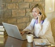Doctor de sexo femenino en su escritorio y en el teléfono Fotos de archivo libres de regalías