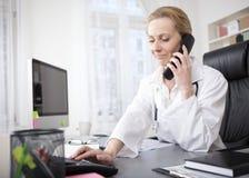 Doctor de sexo femenino en su oficina que marca un teléfono foto de archivo libre de regalías