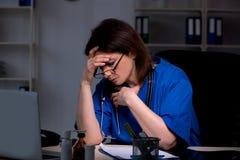 Doctor de sexo femenino envejecido que trabaja en el turno de noche foto de archivo