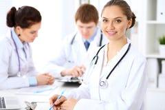 Doctor de sexo femenino feliz que guarda el tablero médico mientras que el personal médico está en el fondo Imágenes de archivo libres de regalías