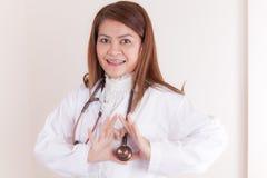 Doctor de sexo femenino feliz que hace forma del corazón imagenes de archivo