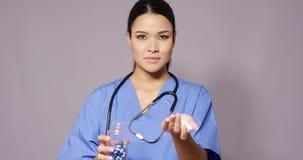 Doctor de sexo femenino hermoso de Latina con el manojo de píldoras metrajes