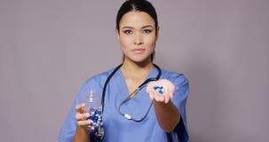 Doctor de sexo femenino hermoso de Latina con el manojo de píldoras almacen de metraje de vídeo