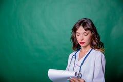 Doctor de sexo femenino hermoso del retrato que sonríe y que completa una carta médica en fondo verde del espacio de la copia Hea fotos de archivo