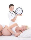 Doctor de sexo femenino hermoso joven con el lyin del reloj y de la mujer embarazada Fotografía de archivo