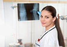 Doctor de sexo femenino hermoso joven en la capa blanca con roentgen en manos fotos de archivo
