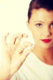 Doctor de sexo femenino hermoso joven que sostiene la píldora rosada Imagen de archivo libre de regalías