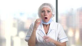 Doctor de sexo femenino hermoso que parece chocado almacen de video