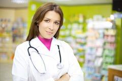 Doctor de sexo femenino hermoso que sonríe en farmacia Imagen de archivo libre de regalías