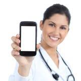 Doctor de sexo femenino hermoso que sonríe y que muestra una pantalla elegante en blanco del teléfono aislada
