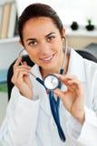 Doctor de sexo femenino hispánico que muestra un estetoscopio Foto de archivo libre de regalías