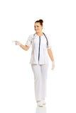 Doctor de sexo femenino integral que señala a la izquierda Imagen de archivo libre de regalías