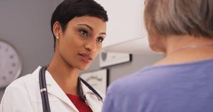 Doctor de sexo femenino inteligente joven que habla con el paciente mayor fotografía de archivo libre de regalías