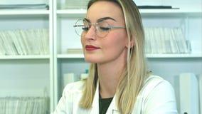 Doctor de sexo femenino joven atractivo en los vidrios que se sientan en el escritorio en oficina almacen de video