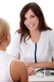 Doctor de sexo femenino joven con el paciente femenino. Foto de archivo libre de regalías
