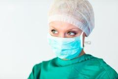 Doctor de sexo femenino joven con la máscara y el casquillo Imagenes de archivo