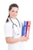 Doctor de sexo femenino joven con las carpetas aisladas en el fondo blanco Imagenes de archivo