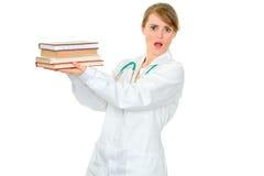Doctor de sexo femenino joven dado una sacudida eléctrica que sostiene los libros médicos fotos de archivo