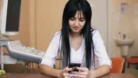 Doctor de sexo femenino joven en la capa blanca del laboratorio que se sienta en el escritorio, usando su smartphone y sonriendo  almacen de metraje de vídeo
