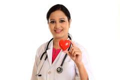 Doctor de sexo femenino joven feliz que lleva a cabo una forma roja hermosa del corazón Fotografía de archivo libre de regalías