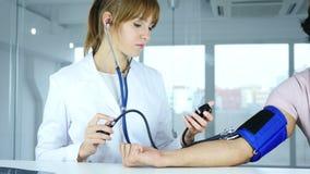 Doctor de sexo femenino joven que comprueba la presión arterial del paciente en clínica almacen de video