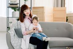 Doctor de sexo femenino joven que examina a un pequeño bebé por el estetoscopio Bebé en la oficina del doctor para el chequeo méd fotos de archivo