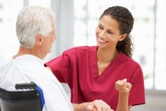 Doctor de sexo femenino joven que habla con el paciente mayor Foto de archivo