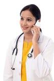 Doctor de sexo femenino joven que habla en el teléfono móvil Fotografía de archivo libre de regalías