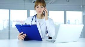 Doctor de sexo femenino joven que lleva a cabo los informes médicos, hablando en el teléfono imagen de archivo