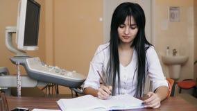 Doctor de sexo femenino joven que se sienta en el escritorio y que escribe la prescripción y que completa los formularios la clín almacen de video