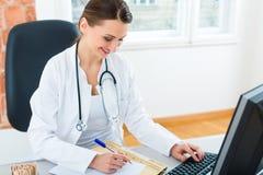Doctor en el escritorio en clínica que escribe un fichero o un expediente Imagen de archivo libre de regalías