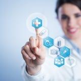 Doctor de sexo femenino joven que usa el interfaz de la pantalla táctil. Fotografía de archivo