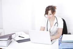 Doctor de sexo femenino joven que usa el ordenador portátil en el escritorio en clínica Imagen de archivo libre de regalías