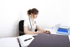 Doctor de sexo femenino joven que usa el ordenador portátil en el escritorio en clínica Foto de archivo