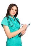 Doctor de sexo femenino joven sonriente en uniforme con la escritura del tablero imagenes de archivo