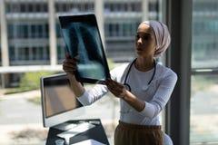 Doctor de sexo femenino de la raza mixta hermosa que mira informe de la radiografía en hospital imagen de archivo libre de regalías