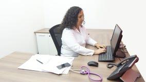 Doctor de sexo femenino latino de sexo femenino que se sienta mirando la pantalla en su oficina con el estetoscopio el escritorio fotografía de archivo