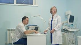 Doctor de sexo femenino mayor que comparte responsabilidades entre el equipo médico Fotografía de archivo