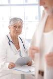 Doctor de sexo femenino mayor que mira al paciente Imágenes de archivo libres de regalías