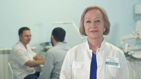 Doctor de sexo femenino mayor que mira la cámara mientras que doctor de sexo masculino que habla con el paciente en el fondo metrajes