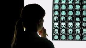 Doctor de sexo femenino pensativo que analiza la exploración de cerebro, investigación médica, caso difícil imagenes de archivo