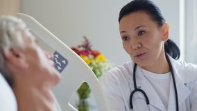 Doctor de sexo femenino positivo que habla con su paciente mayor metrajes
