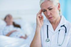 Doctor de sexo femenino preocupante que parece ausente mientras que su reclinación paciente Foto de archivo