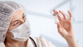 Doctor de sexo femenino profesional en el sitio de hospital que sostiene la botella con el tratamiento Médico de la mujer en el t metrajes