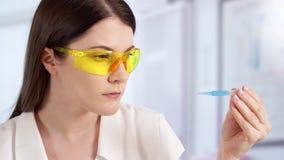 Doctor de sexo femenino profesional en laboratorio con el tratamiento innovador Científico de la mujer en el trabajo metrajes