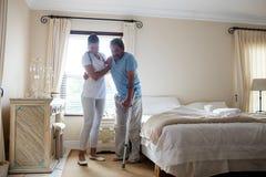 Doctor de sexo femenino que ayuda al hombre mayor a caminar con las muletas en dormitorio Foto de archivo libre de regalías