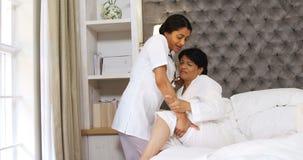 Doctor de sexo femenino que ayuda a la mujer madura en el dormitorio 4k metrajes